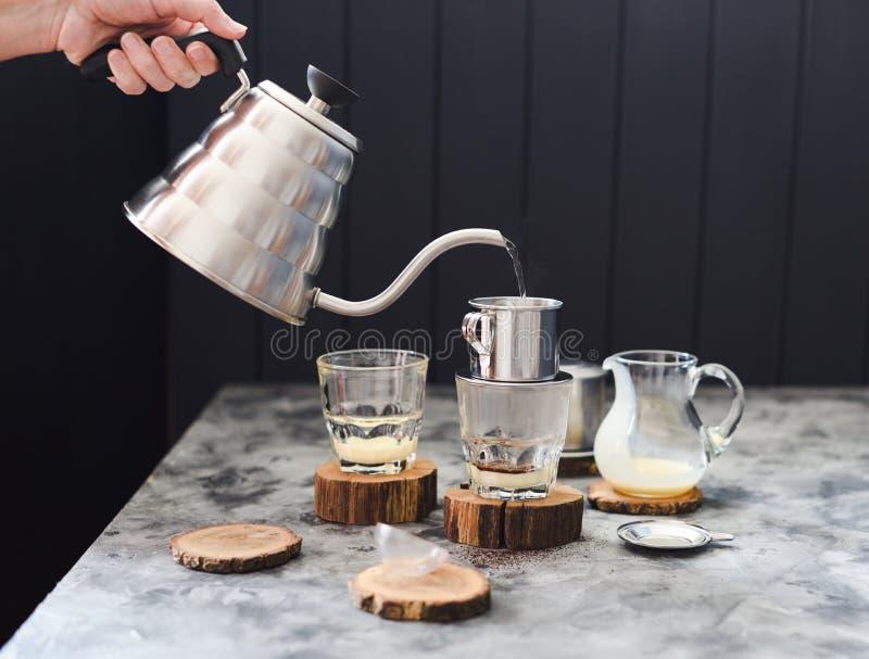 Παραγωγή να χύσει πέρα από το βιετναμέζικο καφέ γάλακτος Χύνοντας νερό χεριών γυναικών από την κατσαρόλα λαιμών χήνων στο phin στ στοκ εικόνα με δικαίωμα ελεύθερης χρήσης