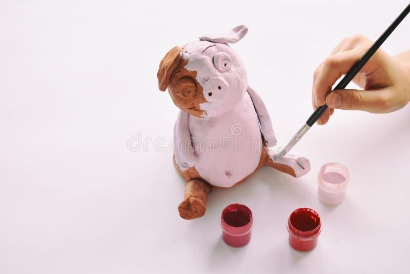 Παραγωγή του παιχνιδιού αργίλου Χοίρος ζωγραφικής με την γκουας Δημιουργικός ελεύθερος χρόνος για τα παιδιά Ενισχυτική δημιουργικ στοκ εικόνα με δικαίωμα ελεύθερης χρήσης