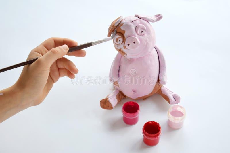 Παραγωγή του παιχνιδιού αργίλου Χοίρος ζωγραφικής με την γκουας Δημιουργικός ελεύθερος χρόνος για τα παιδιά Ενισχυτική δημιουργικ στοκ φωτογραφία με δικαίωμα ελεύθερης χρήσης