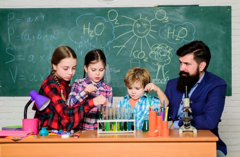 Παραγωγή του πειράματος στο εργαστήριο ή το χημικό γραφείο o εργαστήριο χημείας ευτυχής δάσκαλος παιδιών παιδιά στο παλτό εργαστη στοκ εικόνες