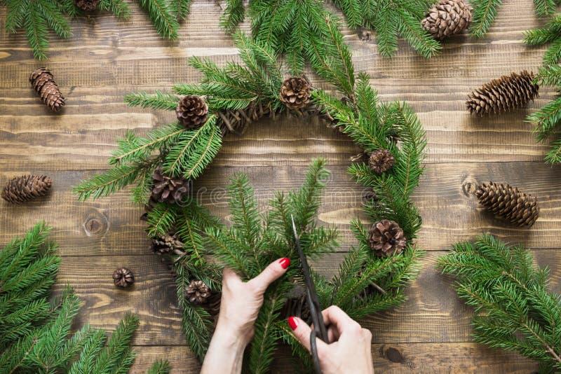 Παραγωγή του στεφανιού Χριστουγέννων που χρησιμοποιεί τα φρέσκα και όλα φυσικά υλικά στοκ εικόνα