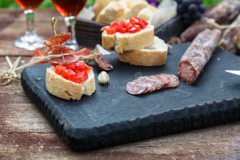 Παραγωγή του pintxo με την ντομάτα και τα λουκάνικα, tapas, ισπανικά τρόφιμα δάχτυλων κομμάτων καναπεδάκια στοκ φωτογραφία με δικαίωμα ελεύθερης χρήσης