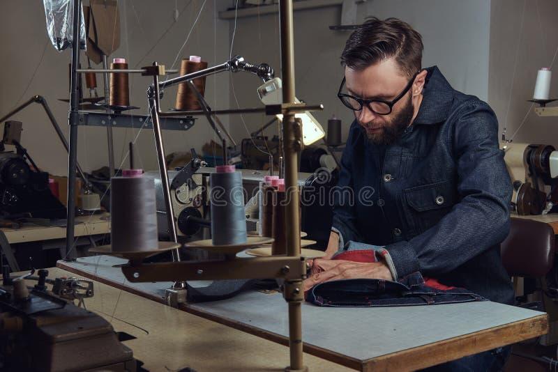 Παραγωγή των ενδυμάτων προσαρμόστε τη συνεδρίαση στον πίνακα και την εργασία σε μια ράβοντας μηχανή στο ράβοντας εργαστήριο στοκ εικόνα με δικαίωμα ελεύθερης χρήσης
