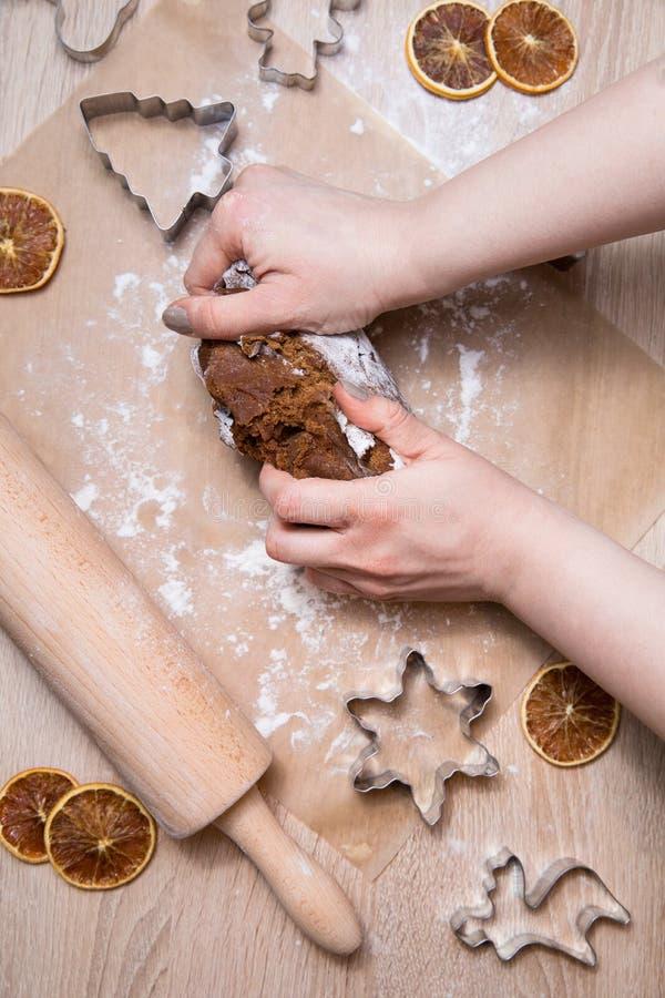 Παραγωγή των μπισκότων μελοψωμάτων Χριστουγέννων, της κοπής μπισκότων και του κυλίσματος στοκ φωτογραφία