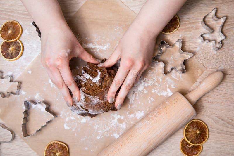 Παραγωγή των μπισκότων μελοψωμάτων Χριστουγέννων, της κοπής μπισκότων και του κυλίσματος στοκ φωτογραφίες