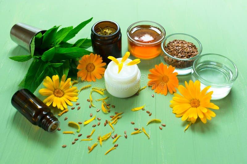 Παραγωγή των φυσικών καλλυντικών Ιατρικά λουλούδια του calendula, chamomile, της μέντας και βοτανικό tincture, πετρέλαιο αρώματος στοκ εικόνες