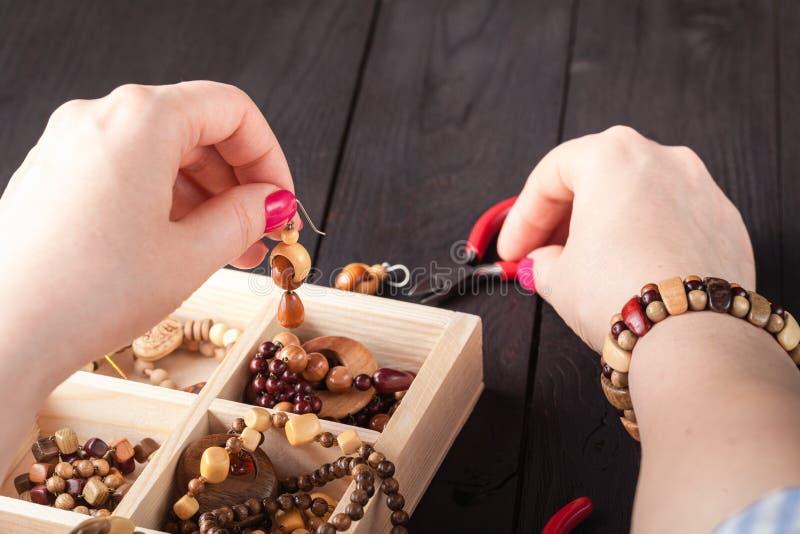 Παραγωγή των χειροποίητων κοσμημάτων Κιβώτιο με τις χάντρες στον παλαιό ξύλινο πίνακα στοκ εικόνα