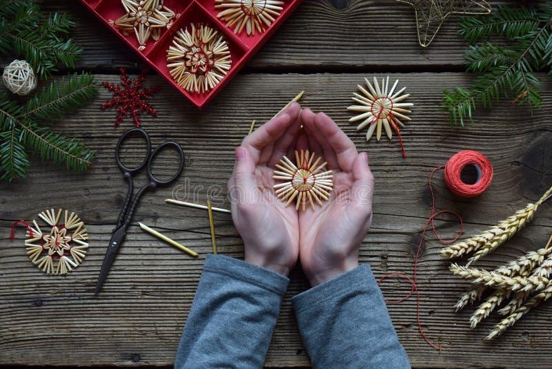Παραγωγή των χειροποίητων παιχνιδιών Χριστουγέννων από το άχυρο με τα χέρια σας Children& x27 έννοια του s DIY Παραγωγή της διακό στοκ εικόνες