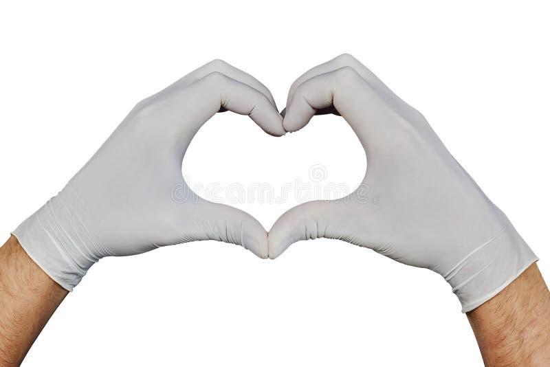 Παραδίδει τα άσπρα ιατρικά γάντια που παρουσιάζουν σημάδι καρδιών που απομονώνεται στο άσπρο υπόβαθρο στοκ εικόνες με δικαίωμα ελεύθερης χρήσης