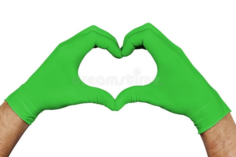 Παραδίδει τα πράσινα ιατρικά γάντια που παρουσιάζουν σημάδι καρδιών που απομονώνεται στο άσπρο υπόβαθρο στοκ εικόνα