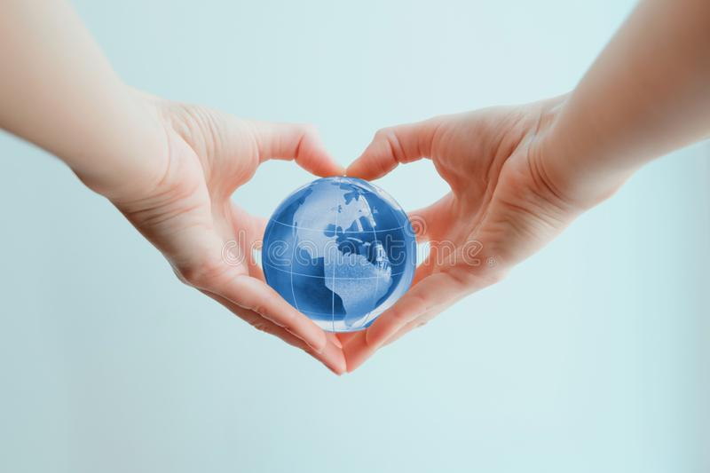 Παραδίδει τη μορφή της καρδιάς που κρατά την μπλε σφαίρα γυαλιού του νότου και της Βόρειας Αμερικής στοκ φωτογραφία με δικαίωμα ελεύθερης χρήσης