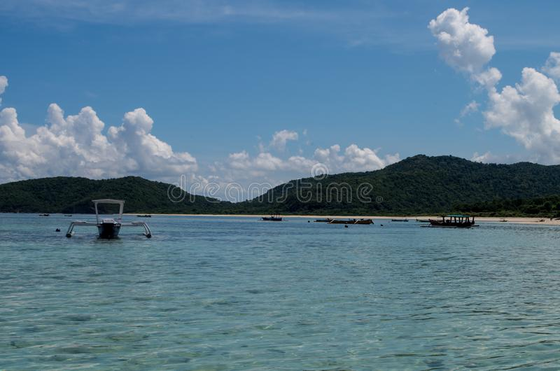 Παραδοσιακά αλιευτικά σκάφη στην παραλία μπροστά από το σκόπελο σημαδιών μέσα στοκ φωτογραφίες με δικαίωμα ελεύθερης χρήσης