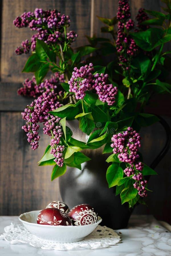 παραδοσιακά διακοσμημένα αυγά Πάσχας στιλβωτικής ουσίας και ιώδη λουλούδια σε ένα βάζο στοκ εικόνα με δικαίωμα ελεύθερης χρήσης