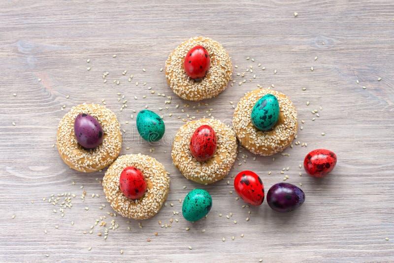 Παραδοσιακά ελληνικά μπισκότα Πάσχας με τους σπόρους σουσαμιού και τα χρωματισμένα αυγά στοκ φωτογραφία