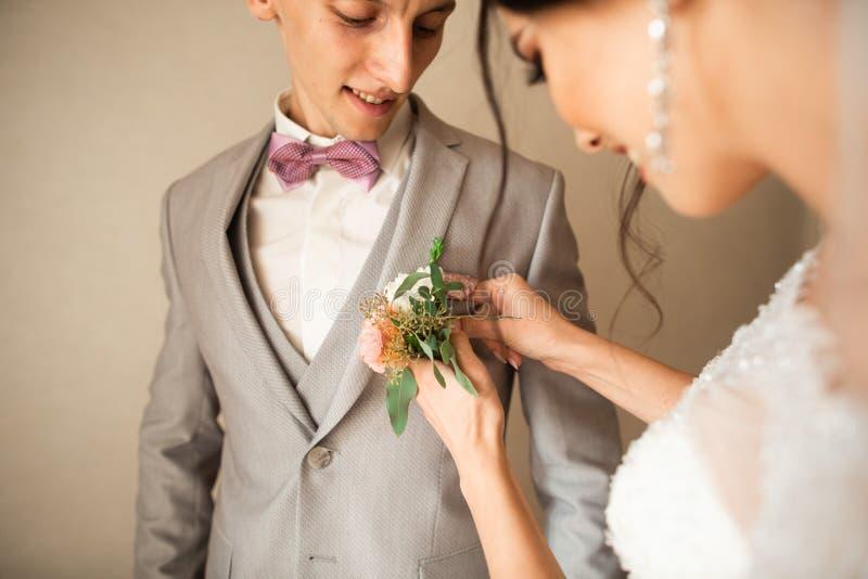 Παραδοσιακά, η νύφη στο σπίτι αγγίζει μια μικρή ανθοδέσμη για το νεόνυμφο Ανθοδέσμη νεόνυμφων δίπλα στο χέρι στο κοστούμι στοκ εικόνα