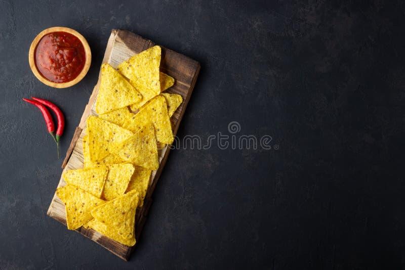 Παραδοσιακά μεξικάνικα nachos τσιπ καλαμποκιού τροφίμων με τη σάλτσα salsa στο μαύρο υπόβαθρο στοκ φωτογραφία με δικαίωμα ελεύθερης χρήσης