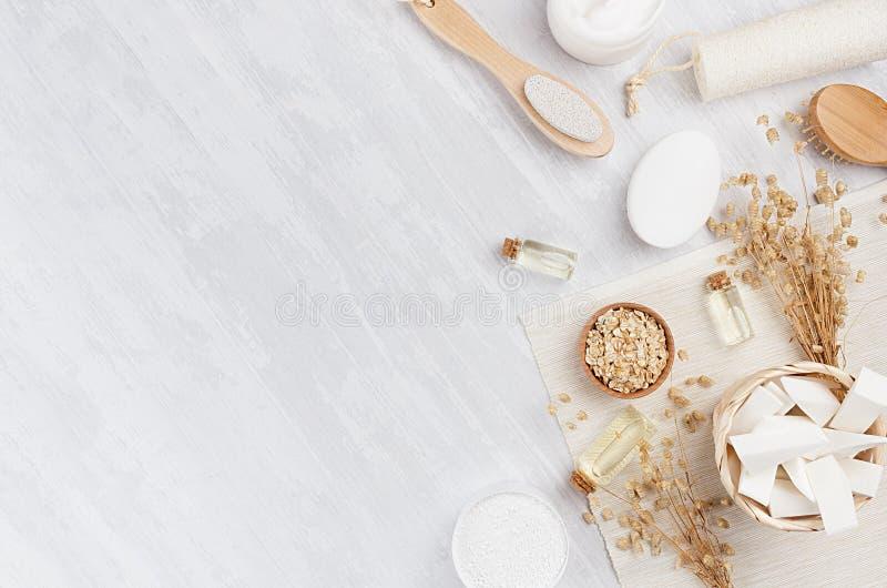 Παραδοσιακά φυσικά αγροτικά προϊόντα καλλυντικών SPA άσπρα και μπεζ εξαρτήματα λουτρών στο ελαφρύ ξύλινο υπόβαθρο, σύνορα, τοπ άπ στοκ εικόνα