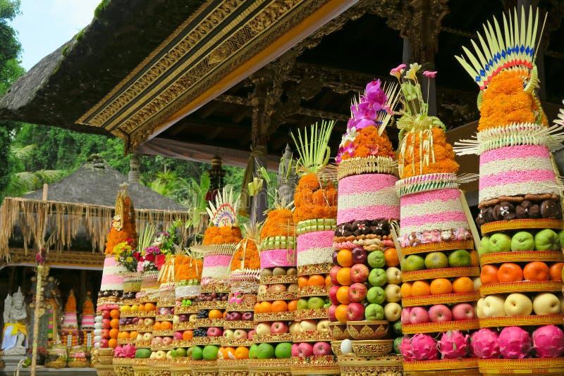 Παραδοσιακές από το Μπαλί εθιμοτυπικές προσφορές ναών: μεγάλες φρούτα και πυραμίδες ρυζιού στα χρυσά πιάτα που διακοσμούνται με τ στοκ εικόνες