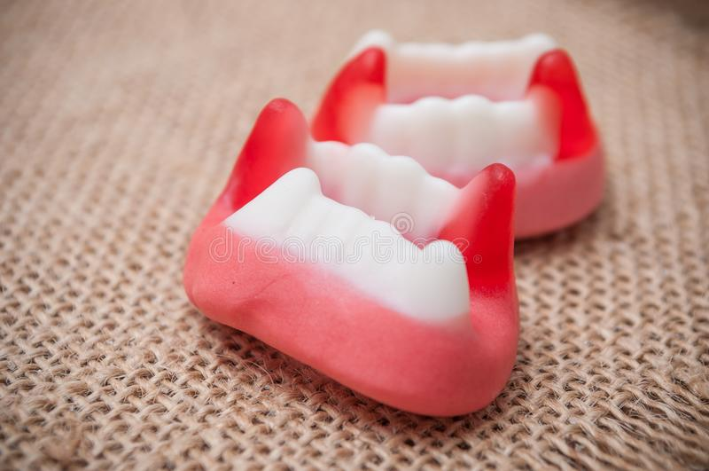 Παραδοσιακές καραμέλες στα διαμορφωμένα δόντια hessian backgr στοκ εικόνα