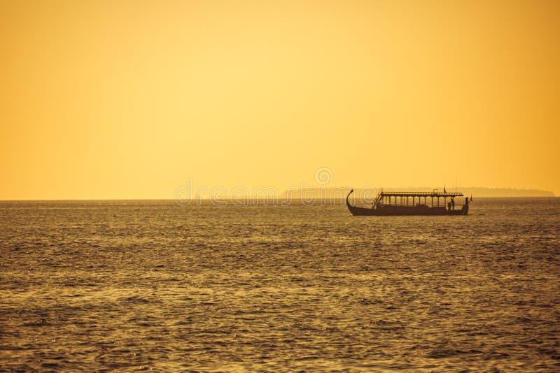 Παραδοσιακή βάρκα Dhoni των Μαλδίβες στη θάλασσα ηλιοβασιλέματος, τους χρυσούς τόνους και το χαλαρώνοντας τροπικό καιρό στοκ εικόνες