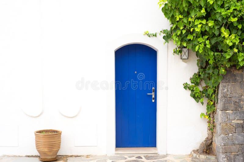 Παραδοσιακή ελληνική μπλε πόρτα με τον άσπρο τοίχο στοκ εικόνες με δικαίωμα ελεύθερης χρήσης