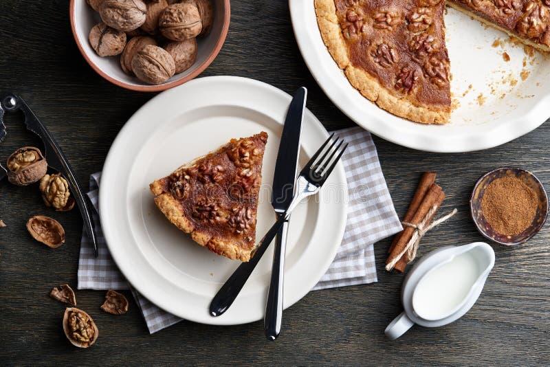 Παραδοσιακή πίτα ξύλων καρυδιάς με τα καρυκεύματα και τα καρύδια στο σκοτεινό ξύλινο πίνακα στοκ φωτογραφίες
