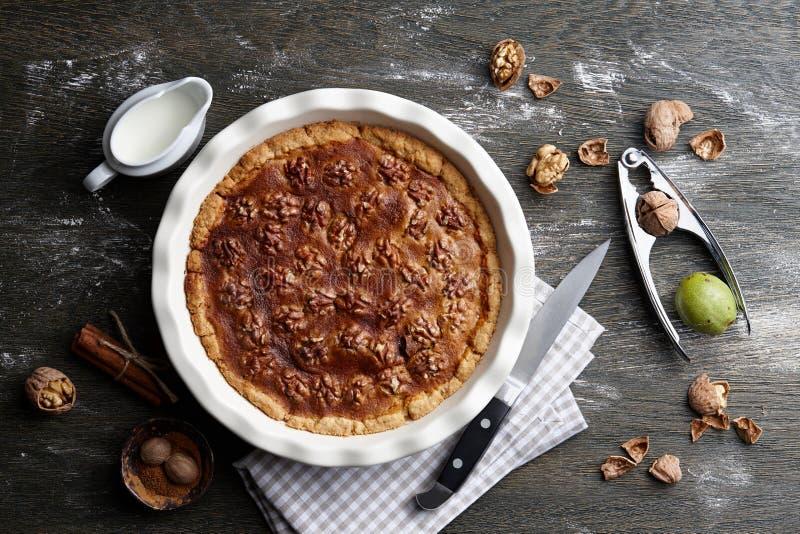 Παραδοσιακή πίτα ξύλων καρυδιάς με τα συστατικά στο σκοτεινό ξύλινο πίνακα στοκ εικόνες