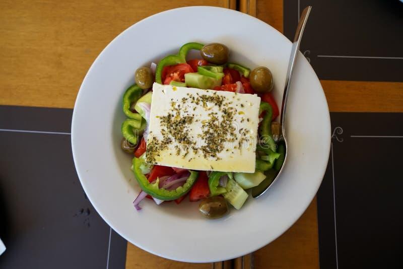 Παραδοσιακή φρέσκια ελληνική σαλάτα με το τυρί φέτας, ντομάτα, αγγούρι, πιπέρι κουδουνιών, κρεμμύδι, ελιά, που ντύνεται με το ελα στοκ φωτογραφία