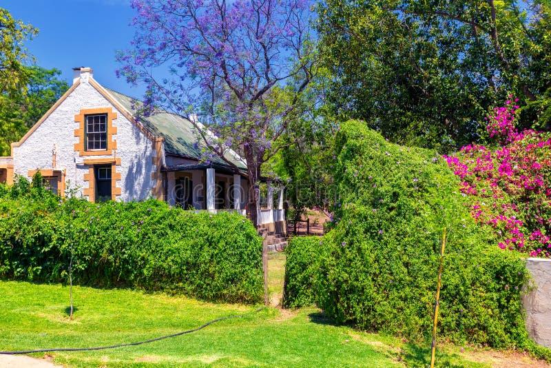 Παραδοσιακοί νοτιοαφρικανικοί σπίτι και κήπος επαρχίας με τα ανθίζοντας δέντρα στοκ φωτογραφία με δικαίωμα ελεύθερης χρήσης