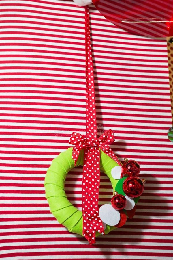 Παραδοσιακό αειθαλές στεφάνι διακοσμήσεων Χριστουγέννων με την κόκκινη κορδέλλα στο κόκκινο ριγωτό υπόβαθρο στοκ φωτογραφία