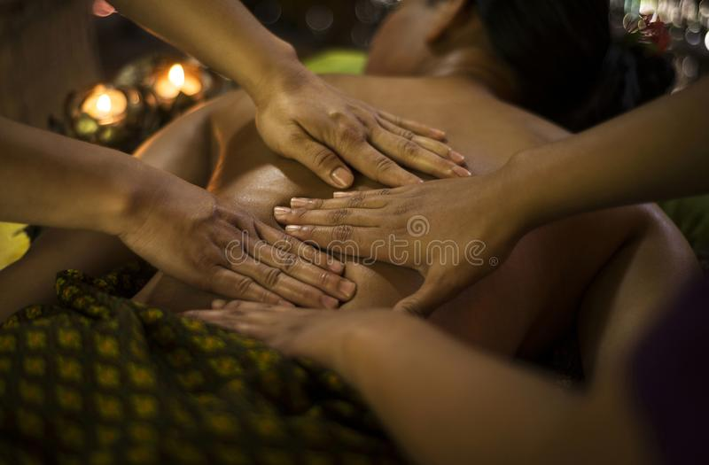 Παραδοσιακό ασιατικό ταϊλανδικό μασάζ τεσσάρων χεριών στην τροπική SPA στοκ εικόνες