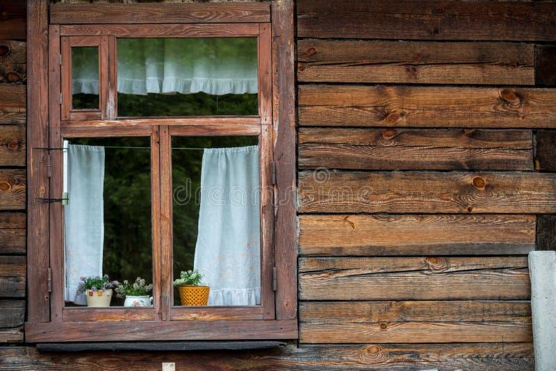 Παραδοσιακό εκλεκτής ποιότητας παλαιό καφετί ξύλινο παράθυρο πλαισίων με τις κουρτίνες και τα λουλούδια στον ξύλινο τοίχο στοκ εικόνες με δικαίωμα ελεύθερης χρήσης