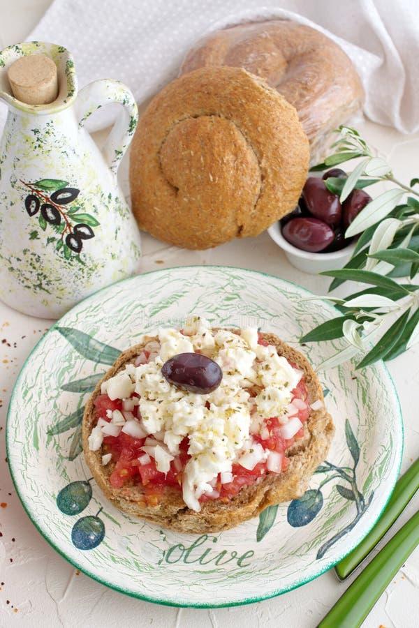 Παραδοσιακό ελληνικό ορεκτικό Dakos σε ένα παραδοσιακό πιάτο με το κεραμικό βάζο ελαιολάδου, το ξηρό ψωμί σίκαλης, τις ελιές και  στοκ φωτογραφία