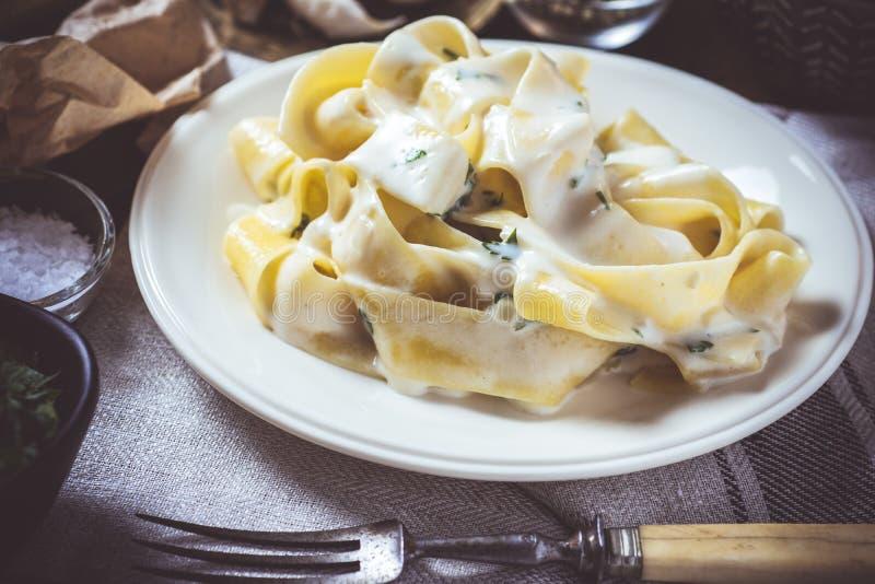 Παραδοσιακό ιταλικό πιάτο ζυμαρικών του Alfredo με την κρεμώδη σάλτσα τυριών και βασιλικού στοκ εικόνα