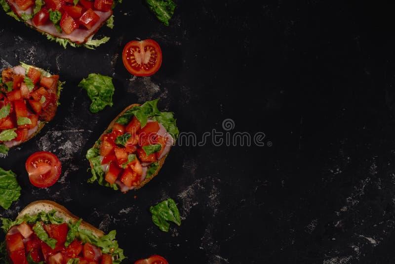 Παραδοσιακό ιταλικό Bruschetta με τις τεμαχισμένες ντομάτες, τη σάλτσα μοτσαρελών, τα φύλλα σαλάτας και το ζαμπόν σε ένα σκοτεινό στοκ εικόνες