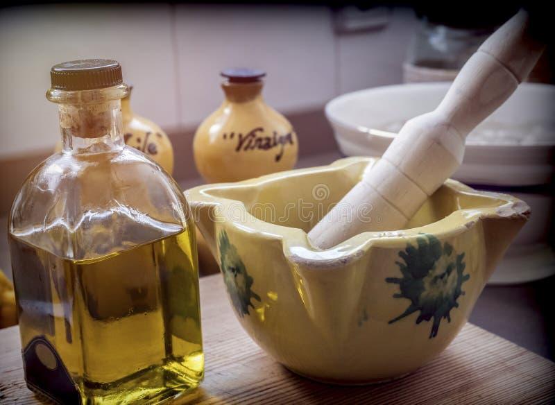 Παραδοσιακό κεραμικό κονίαμα δίπλα σε ένα μπουκάλι του ελαιολάδου σε μια κουζίνα στοκ εικόνα