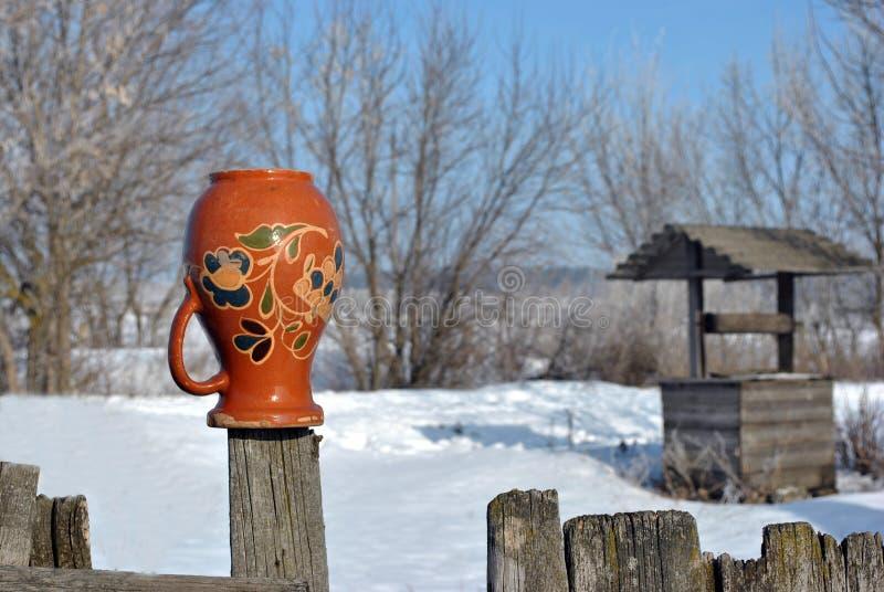 Παραδοσιακό ουκρανικό αγροτικό τοπίο με έναν ξύλινο καλά και φράκτης με την ένωση της στάμνας σε το με τη λαϊκή ζωγραφική Petryki στοκ εικόνα