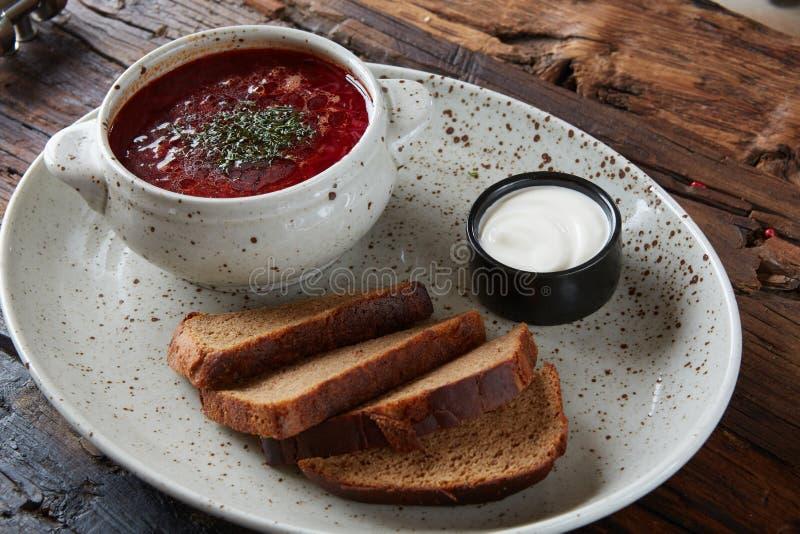 Παραδοσιακό ουκρανικό ρωσικό borscht με τα άσπρα φασόλια στο κύπελλο Πιάτο borsch σούπας ρίζας κόκκινων τεύτλων στο μαύρο rustick στοκ εικόνες