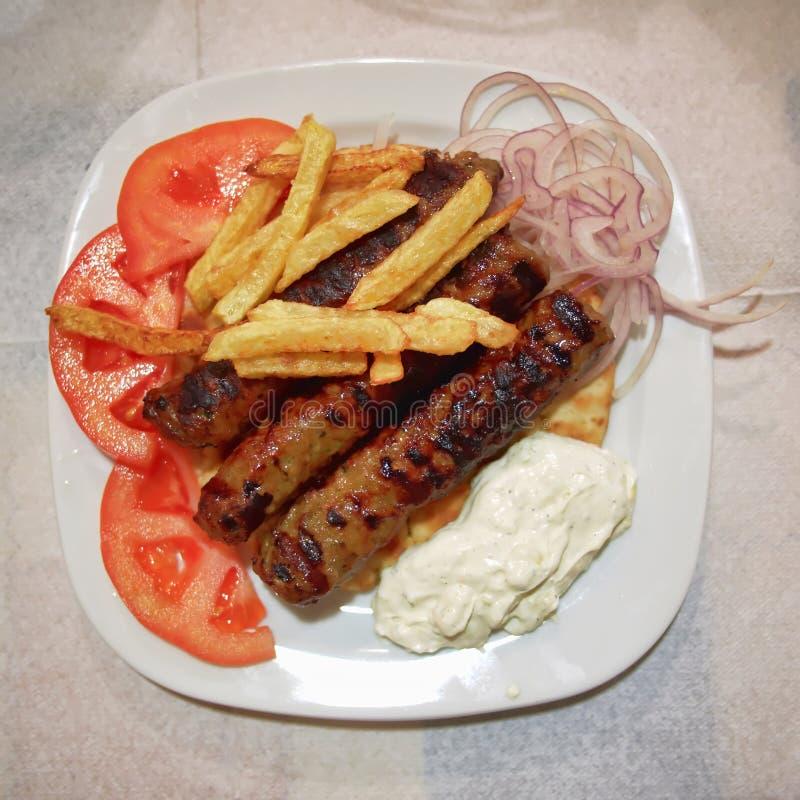 Παραδοσιακό πιάτο Kebab, με τις μπριζόλες κρέατος, την ντομάτα τηγανητών και το tzatziki στοκ φωτογραφίες