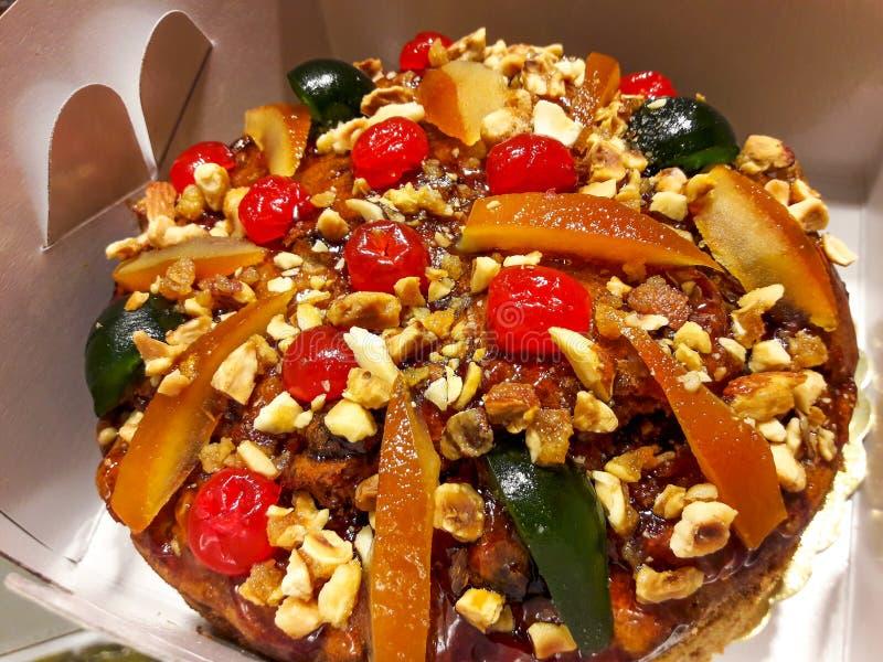 Παραδοσιακό σπιτικό κέικ Χριστουγέννων στο κιβώτιο με τα φρούτα και τα καρύδια στοκ εικόνα με δικαίωμα ελεύθερης χρήσης