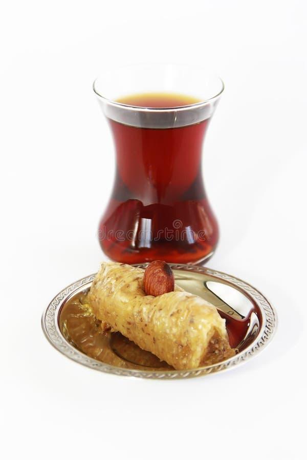 Παραδοσιακό τουρκικό γλυκό με τα καρύδια baklava και τουρκικό τσάι σε μια κούπα γυαλιού στοκ εικόνες