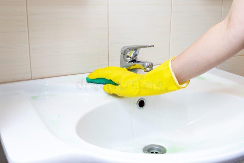 Παραδώστε τον κίτρινο λαστιχένιο νεροχύτη λουτρών πλυσιμάτων γαντιών με ένα σφουγγάρι Καθαρίστε επάνω την έννοια στοκ φωτογραφίες με δικαίωμα ελεύθερης χρήσης