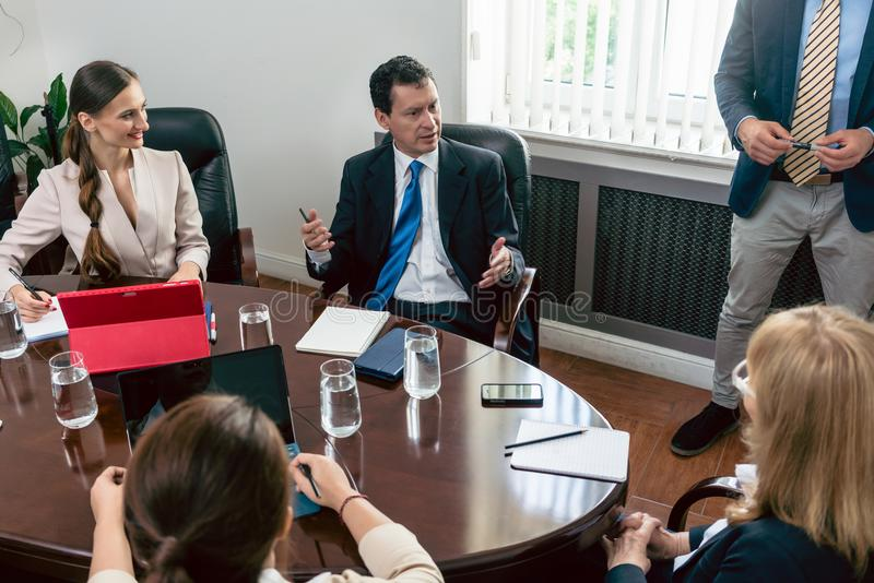 Παραισθησιακός διευθυντής που μοιράζεται τις ιδέες του κατά τη διάρκεια μιας επίσημης συνεδρίασης στοκ φωτογραφία