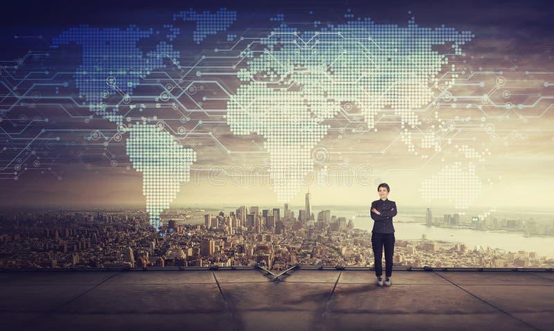 Παρακινημένη επιχειρηματίας στη στέγη του ουρανοξύστη Χρόνος ηλιοβασιλέματος και προβολή ολογραμμάτων παγκόσμιων χαρτών στον ουρα στοκ εικόνες