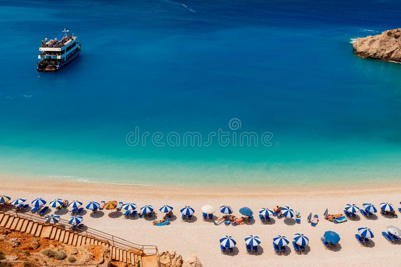 Παραλία άμμου θάλασσας με τους τουρίστες κάτω από τις ομπρέλες που κάνουν ηλιοθεραπεία και βάρκα ταξιδιού στο νερό στοκ εικόνες