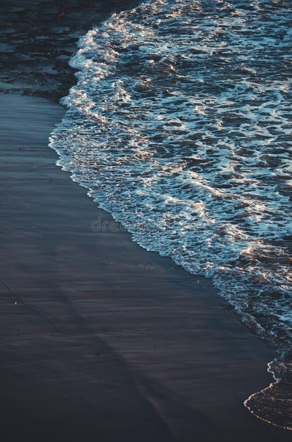 παραλία άμμου με τις πέτρες και τον αφρό του κύματος στο ηλιοβασίλεμα Fuerteventura στοκ φωτογραφίες