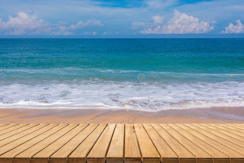 Παραλία άμμου με το ξύλινο πάτωμα, την μπλε θάλασσα και τον ουρανό στοκ εικόνα