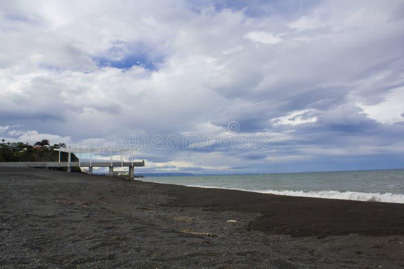 Παραλία Ειρηνικών Ωκεανών με τη σκοτεινή άμμο στοκ φωτογραφία