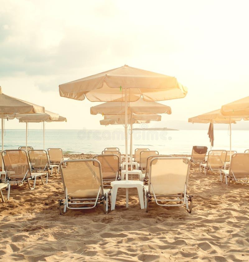 Παραλία θάλασσας με τις ομπρέλες και sunbeds Έννοια καλοκαιρινών διακοπών και χαλάρωσης στοκ φωτογραφία