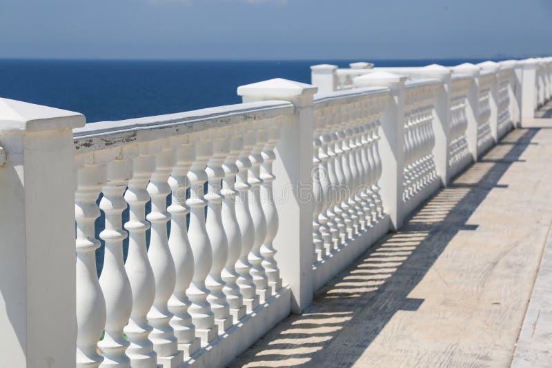 Παραλία κάγγελων Άσπρες στήλες που αγνοούν τη θάλασσα Άποψη των άσπρων στυλοβατών και horizont σχετικά με την μπλε θάλασσα και το στοκ φωτογραφία